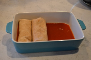 layer in a pan with enchilada sauce, top with more enchilada sauce and a small amount of cheese